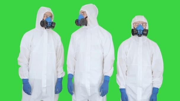 Team von Wissenschaftlern oder Ärzten in Schutzanzügen bereit für die Arbeit, Hände kreuzend auf einem Green Screen, Chroma Key.