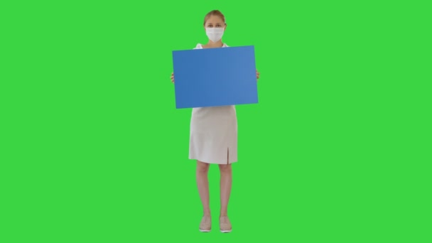 Businesswoman in medical mask holding blank board sign on a Green Screen, Chroma Key.