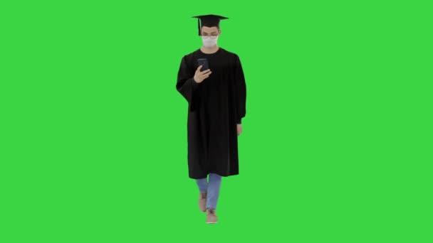 Fiatal férfi ballagási köpenyben sétál orvosi maszkban okostelefonnal a zöld képernyőn, Chroma Key.