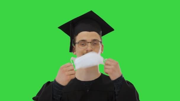 Boldog férfi raduációs köpenyben orvosi maszkot vesz le Vírus egy zöld képernyőn, Chroma Key.