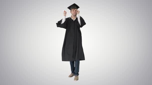 Absolvent je držitelem diplomu a pózuje s ním na fotografii na gradientním pozadí.