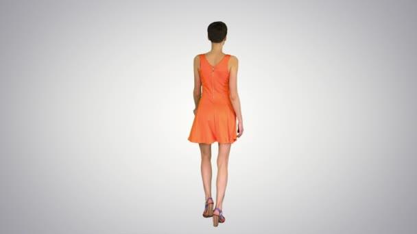 Girl Dancing in Orange SunDress on gradient background.