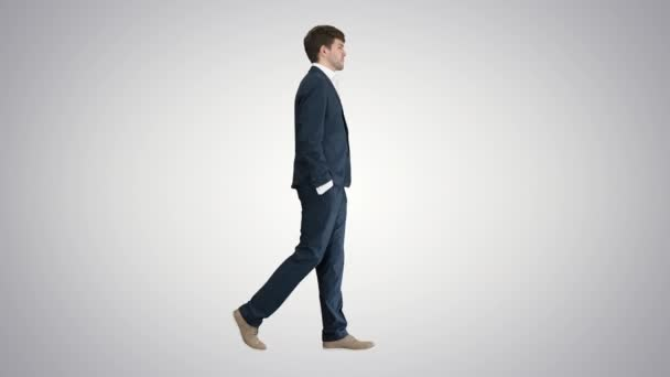 Handsome business man walking with his hands in pockets on gradient background.
