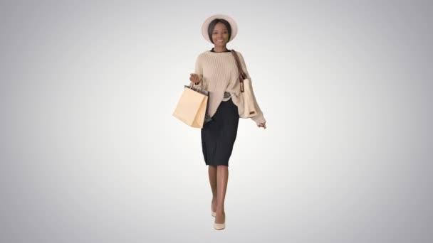 Šťastný mladý africký americký žena chůze s nákupy na gradient pozadí.