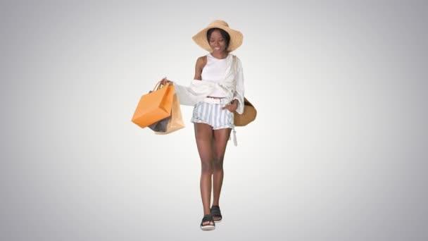 Stylový mladý afro žena chůze s nákupními taškami na gradient pozadí.
