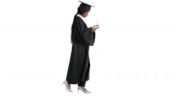 Mladý afro americká dívka student oblečený v černé maturitní šaty držící diplom a pomocí mobilního telefonu na bílém pozadí.