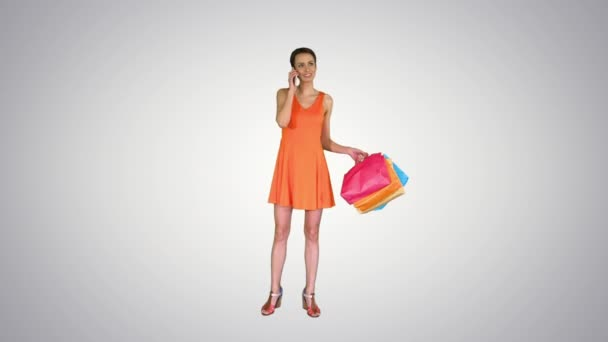 Young woman holding shopping and making a phone call on gradient background.
