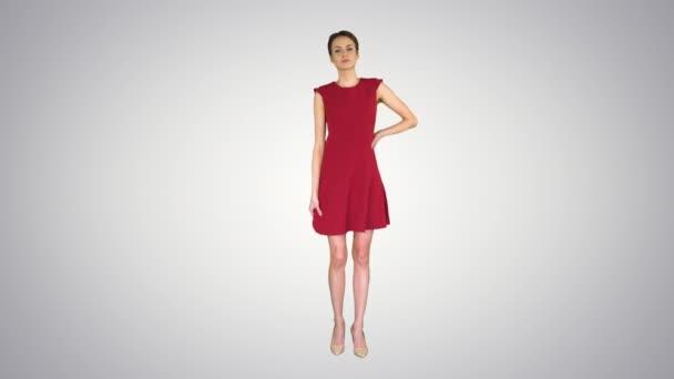 Schöne junge Frau mit kurzen Haaren in rotem Kleid posiert auf Gradienten Hintergrund.