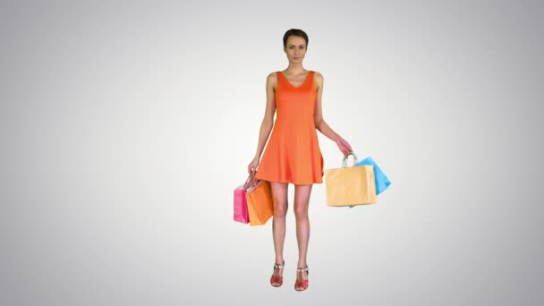 Žena pózuje na kameře s pestrobarevnými nákupních tašek na gradientu pozadí.