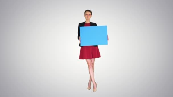 Podnikatelka drží prázdné tabuli znamení na pozadí přechodu.