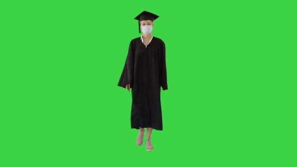 Női diploma a kapitány és a ruha viselése orvosi maszk séta a zöld képernyőn, Chroma Key.
