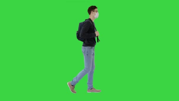 Student in protective masks walking with backpack on a Green Screen, Chroma Key.