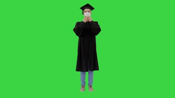 Fiatal férfi ballagási köpenyben orvosi maszkban egy zöld vásznon, Chroma Key.
