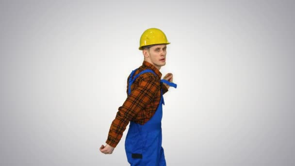 Dancing young engineer with helmet after work on gradient background.