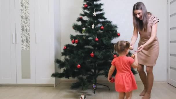 Frohe Weihnachten und frohe Feiertage. Mutter und Tochter schmücken den Weihnachtsbaum drinnen. der Morgen vor Weihnachten.