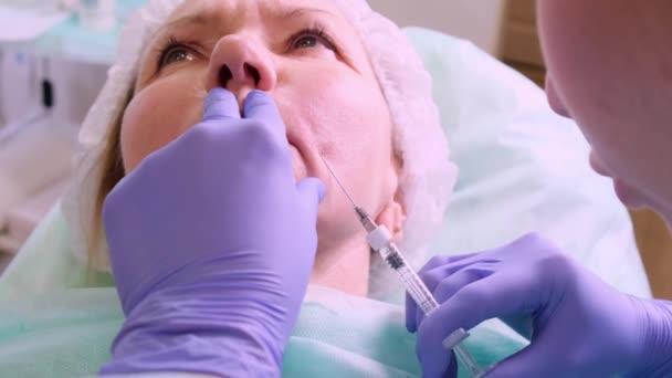Középkorú nő 50 kap egy emelés injekció hialuronsav az arcba egy orvos kozmetológus. Kozmetikai eljárás. közelkép
