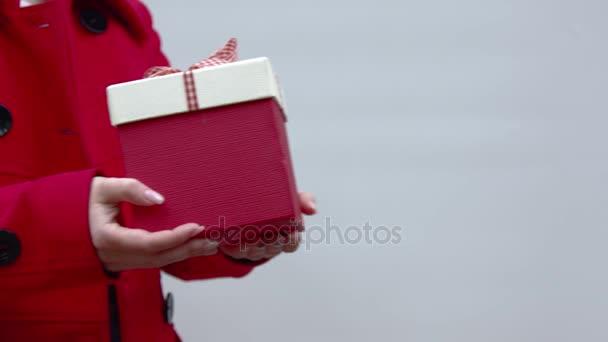 piros ajándék doboz fehér szalaggal.