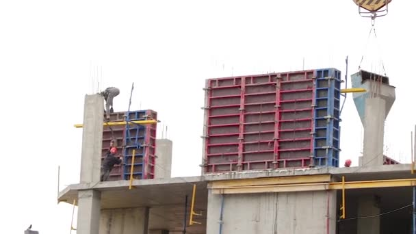 Builders build a multi-storey house using a construction crane. Workers install walls in a new building under construction.