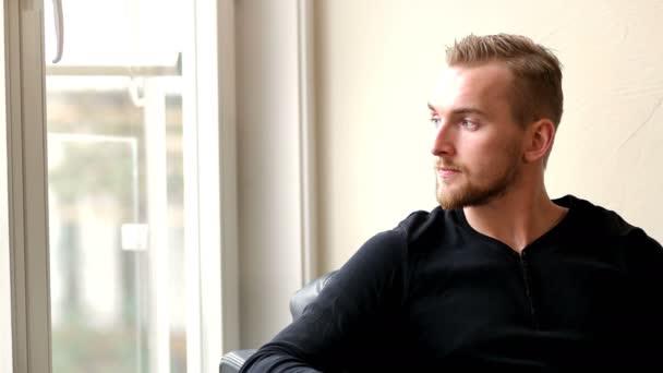 Szép ember ül a szobában