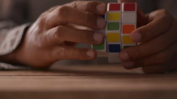 Zblízka ruce obchodníka řešení rubik kostky puzzle na stole. Řešení problémů při koncepci práce.