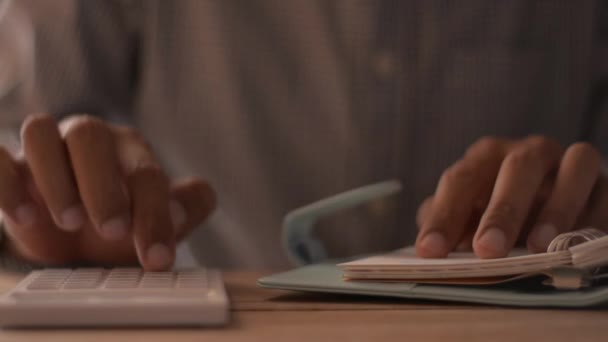 Nahaufnahme eines Mannes, der auf dem Schreibtisch seine Ausgaben berechnet. Finanzen, Investitionen, Wirtschaft, Sparen oder Versicherungskonzept.