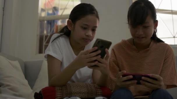 Dvě krásné dívky jsou těšit hrát hry na mobilním telefonu a posezení na pohovce během karantény doma. Koncept koníčků a aktivit.
