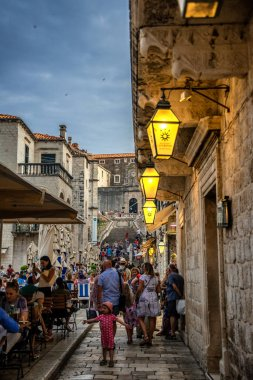 People at street cafe with lantern illuminated at night in Dubrovnik, Croatia