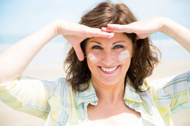 Funny woman protecting skin from sun