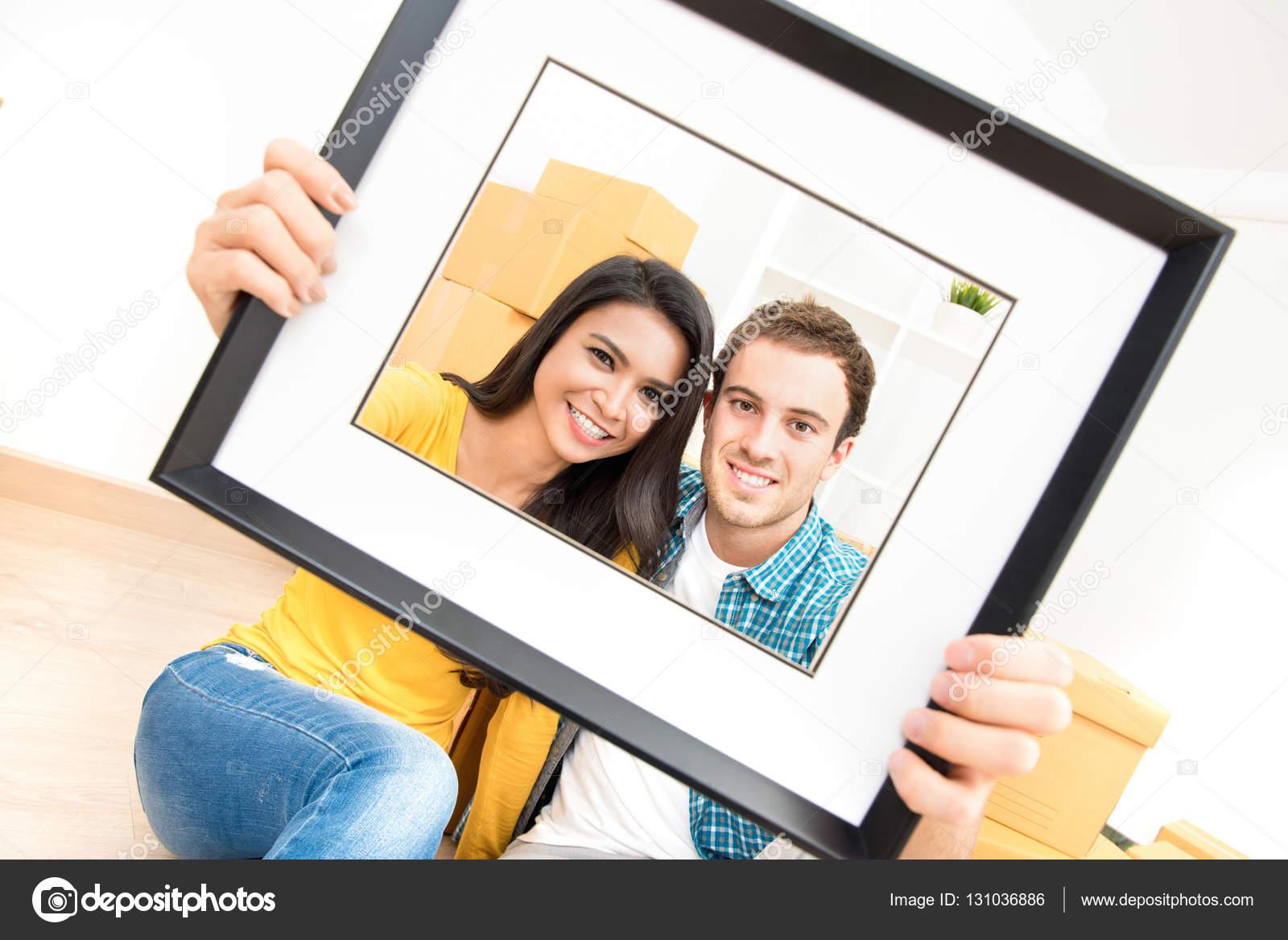 Pareja interracial feliz sonriendo a través de marco — Fotos de ...