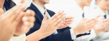 Group of business people clapping their hands at the meeting