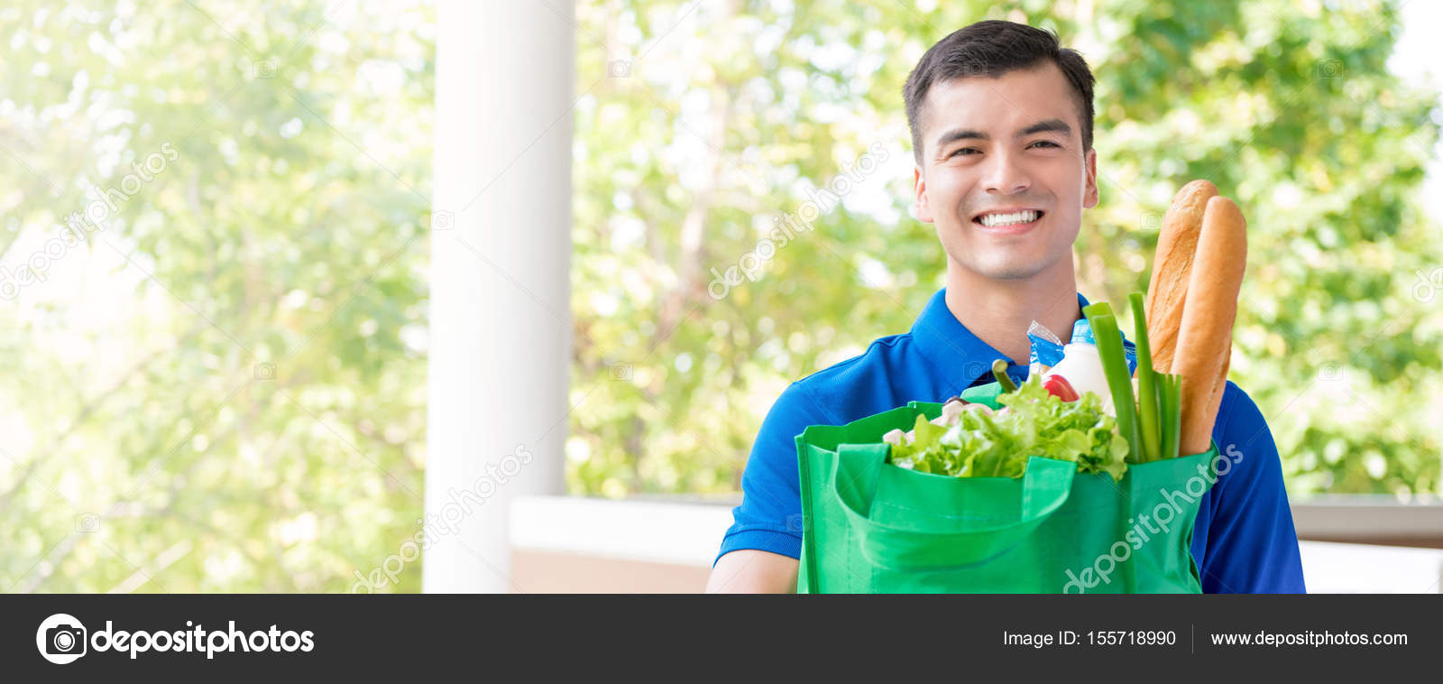 Smiling delivery man holding recycle grocery shopping bag
