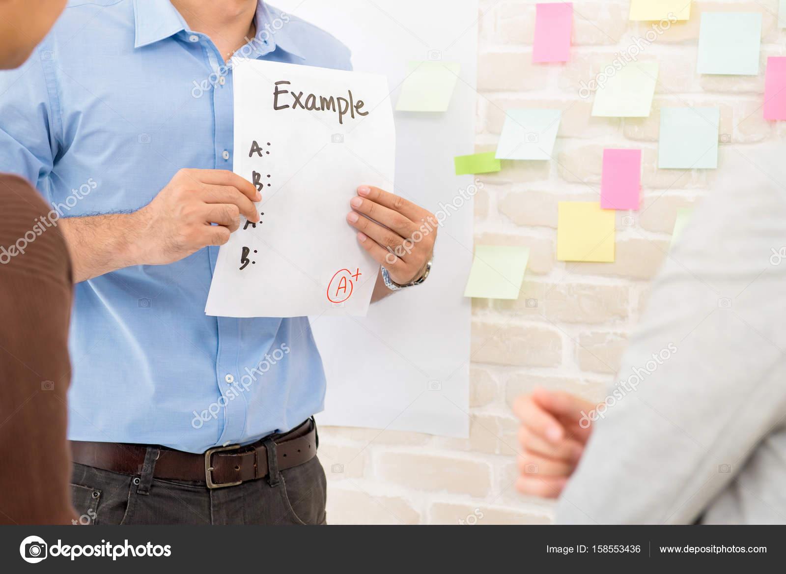 Lehrer zeigt Beispiel Papier Studenten dabei Gruppenarbeit ...