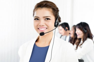 Smiling woman wearing microphone headset as an operator, telemarketer, call center or customer service staff stock vector
