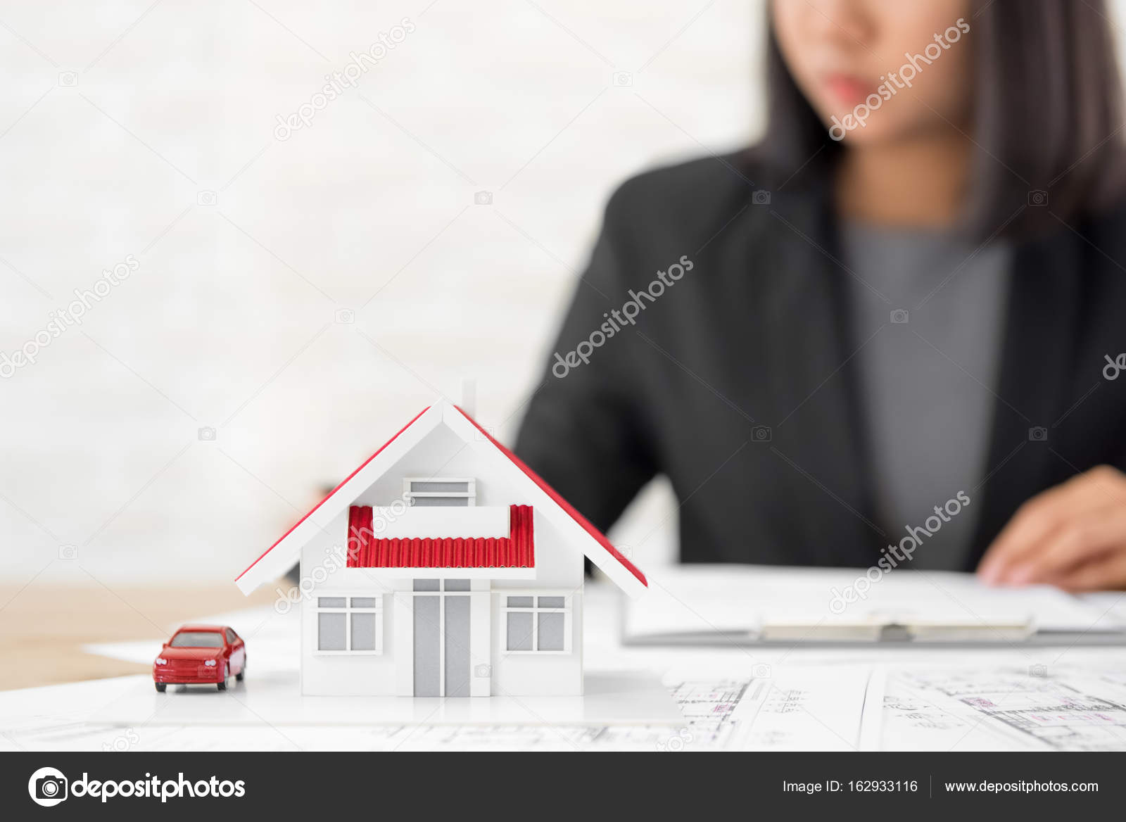 House model on blueprint paper at the table with blurred busines house model on blueprint paper at the table with blurred businesswoman in background real estate and property agent concept photo by kritchanut malvernweather