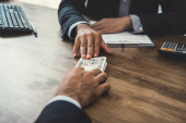 Podnikatel dává peníze, japonské jenové bankovky, svému partnerovi u stolu při uzavírání kontraktu - úvěry, úplatky a korupce