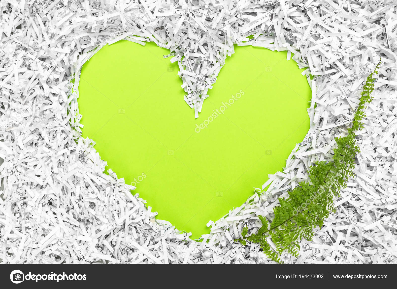 heart frame made of shredded paper and a green leaf stock photo