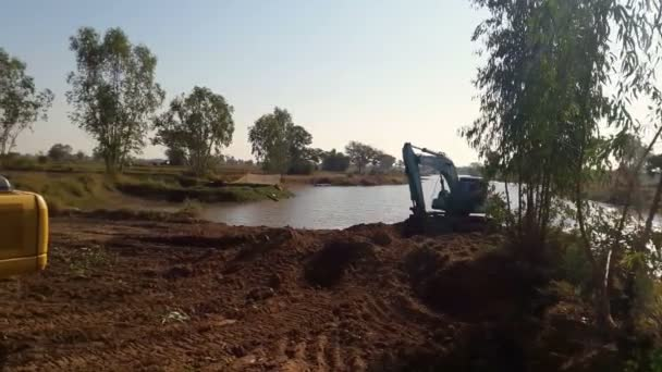 Backhoe dredging the river in the countryside.