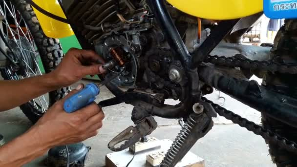 Mechanic repairing the electrical system in the motorcycle.