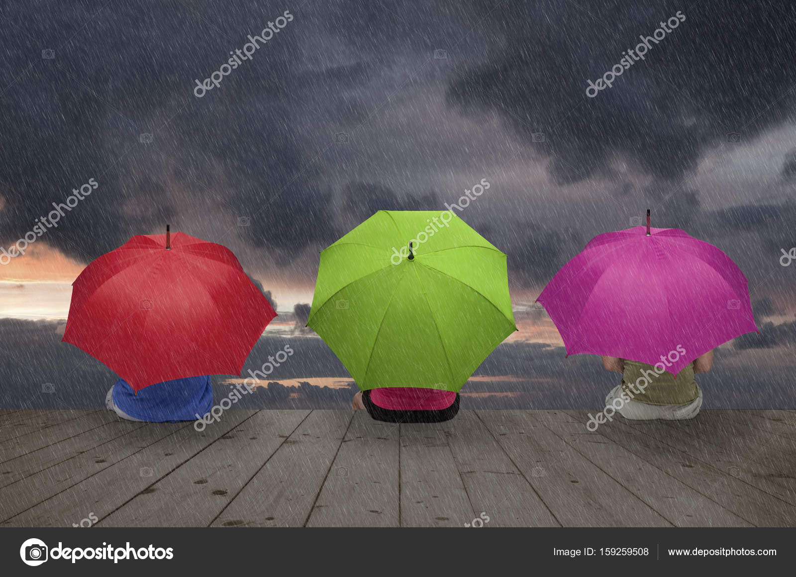 79494c9058 Drei Personen sind unter Sonnenschirmen gegen den Regen versteckt.