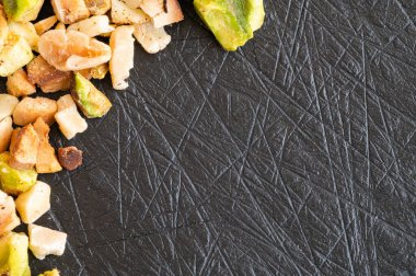 Toasted pistachio grain and chopped hazelnuts over a black slate board with space for text
