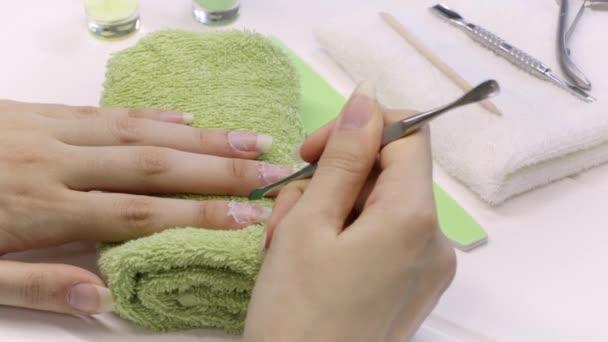Maniküre. Schieben Sie die Nagelhaut mit einem Metallschieber zurück. Maniküre-Werkzeuge, Nagellack, Öl. Nagelpflege zu Hause, SPA, Schönheit. Lange Naturnägel. Schönheitssalon.