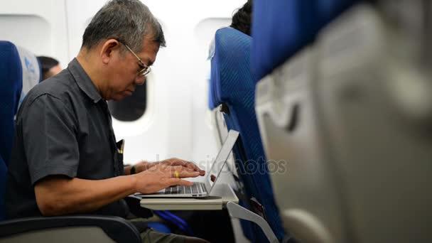 Starší Asiat pomocí přenosného počítače v letu