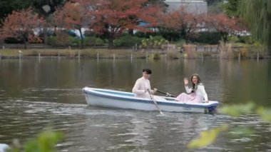 Young couples row boats in autumn Ueno park, Tokyo, Japan