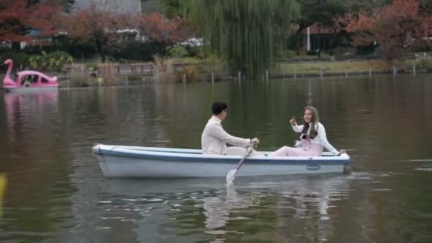 Young couples with romantic tour on the autumn lake
