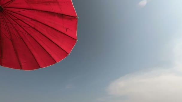 schöner roter Sonnenschirm auf blauem Himmel