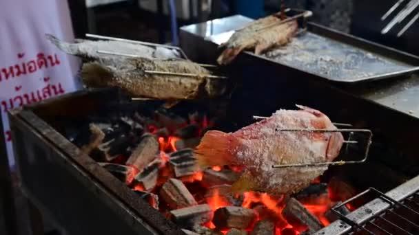 4k Solené grilované ryby válcované s kamny na dřevěné uhlí s plamenem