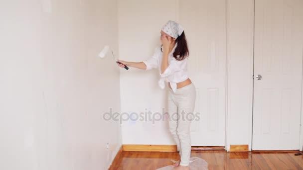 die junge Frau malt den Raum in weißer Farbe und lächelt