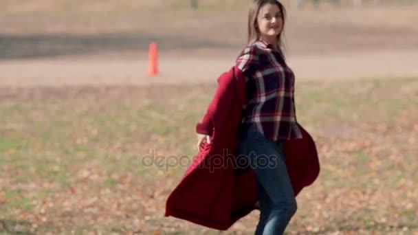 Šťastná žena v podzimním parku. Radostné a nadšený mladá žena baví házet žluté listy v parku slunečný podzim