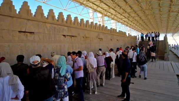 PERSEPOLIS, IRAN - OCTOBER 13, 2017: The crowded area at the wall of Eastern Stairs of Apadana palace, tourists enjoy the ancient reliefs, on October 13 in Persepolis.