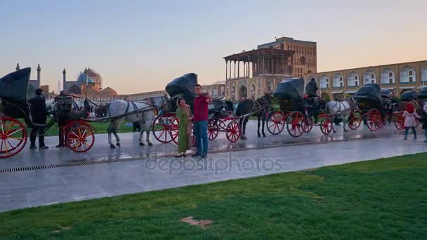 ISFAHAN, IRAN - OCTOBER 19, 2017: The twilight over the crowded Naqsh-e Jahan Square, the popular place for the walks among locals and tourists, enjoying the horse carriages, on October 19 in Isfahan.